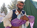 A man holds a sick child in his arms, Pakistan