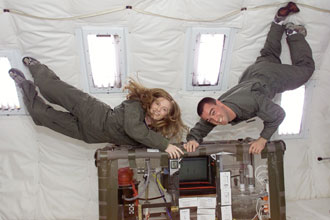 Two university students with an experiment onboard the reduced gravity aircraft.