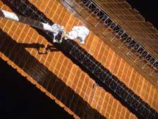 Astronaut repairs solar wing.