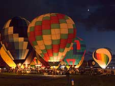 Colorful balloons light up for the Balloon Glow event at the International Balloon Fiesta as the moon peeks from behind the clouds.
