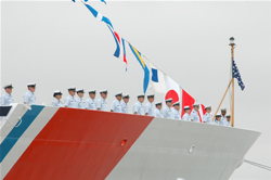 The crew of the USCG Cutter Bertholf man the rails during the commissioning ceremony on Coast Guard Island
