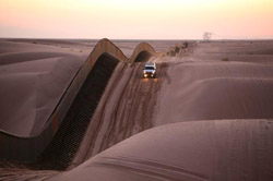A CBP vehicle rides the dunes along the edge of the border fence.