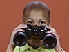 A boy holding a pair of binoculars