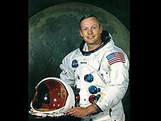 Armstrong in a white spacesuit in front of a picture of the moon