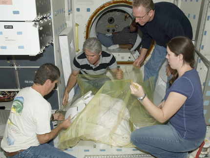 United Space Alliance technicians Troy Mann, Mark Shimei, Jim Smodell and Kelly Gattuso carefully wrap the lower portion of an Extravehicular Mobility Unit (EMU) spacesuit prior to removal from Space Shuttle Endeavour.