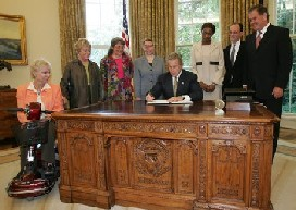 President George W. Bush signs an executive order for individuals with disabilities in emergency preparedness on July 22, 2004 in the Oval Office.
