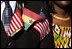 Flags of the United States and Ghana are displayed by a guest attending the South Lawn Arrival Ceremony for President John Agyekum Kufuor of Ghana Monday, Sept. 15, 2008, at the White House.