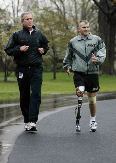 President George W. Bush runs with U.S. Army Staff Sergeant Michael McNaughton, of Denham Springs, La., on the South Lawn of the White House Wednesday, April 14, 2004. The two met January 17, 2003, at Walter Reed Army Medical Center, where SSgt. McNaughton was recovering from wounds sustained in Iraq. The President then wished SSgt. McNaughton a speedy recovery so that they might run together in the future. White House photo by Eric Draper