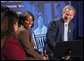President George W. Bush receives praise from Welfare to Work graduate Ann Briscoe and her husband Alfred at an East Room event at the White House on June 4, 2002.