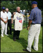 President George W. Bush holds up a commemorative baseball jersey with Jackie Robinson's number 42 presented to him by players from Robinson's playing era at the White House Tee Ball Game Sunday, July 15, 2007. Tee Ball players wore the number 42 to celebrate the legacy of Jackie Robinson. More about Tee Ball on the South Lawn. White House photo by Chris Greenberg