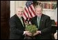 President George W. Bush accepts a bowl of shamrocks from Irish Prime Minister Bertie Ahern during a ceremony celebrating St. Patrick's Day in the Roosevelt Room Thursday, March 17, 2005.  White House photo by Paul Morse
