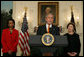 """Flanked by Secretary of State Condoleezza Rice and Mrs. Laura Bush, President George W. Bush delivers a statement at the White House Friday, Oct. 19, 2007, regarding sanctions on Burma. Said the President, """"The people of Burma are showing great courage in the face of immense repression. They are appealing for our help. We must not turn a deaf ear to their cries."""" White House photo by Chris Greenberg"""