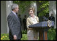 """Laura Bush looks over to President Bush during a Rose Garden announcement honoring the 2005 Preserve America Presidential Awards Winners Monday, May 2, 2005. """"These awards recognize collaborative efforts to protect and enhance our nation's cultural and historical heritage,"""" said Mrs. Bush in her remarks. White House photo by Eric Draper"""