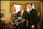 President George W. Bush holds a racing helmet as he poses with 2007 NASCAR Nextel Cup Champion Jimmie Johnson and wife, Chandra Johnson Tuesday Feb. 5, 2008, in the Oval Office. White House photo by Chris Greenberg
