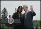 President George W. Bush and Kim Oliver, the 2006 National Teacher of the Year, wave from the podium on the South Lawn Wednesday, April 26, 2006, during a ceremony honoring the Silver Spring, Maryland kindergarten teacher.  White House photo by Paul Morse