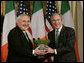 President George W. Bush is presented with a bowl of shamrocks by Ireland's Prime Minister Bertie Ahern at a ceremony in the Roosevelt Room at the White House, March 16, 2007. White House photo by Joyce N. Boghosian