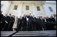 """President George W. Bush is surrounded by members of the House Republican Conference on the steps of the North Portico Thursday, March 29, 2007, as he delivers a statement on the budget and the emergency supplemental after meeting with the group. Said the President, """"We stand united in saying loud and clear that when we've got a troop in harm's way, we expect that troop to be fully funded; and we've got commanders making tough decisions on the ground, we expect there to be no strings on our commanders; and that we expect the Congress to be wise about how they spend the people's money.""""  White House photo by Eric Draper"""