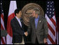 President George W. Bush exchanges handshakes with Prime Minister Shinzo Abe of Japan after their joint press availability Friday, April 27, 2007, at Camp David.  White House photo by Joyce N. Boghosian
