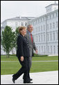 President George W. Bush walks with Germany's Chancellor Angela Merkel as the two leaders met for lunch Wednesday, June 6, 2007, at the Kempinski Grand Hotel in Heiligendamm, Germany.  White House photo by Eric Draper