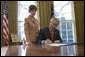 Laura Bush stands by President George W. Bush as he signs S. 843, the Combating Autism Act of 2006, in the Oval Office Tuesday, Dec. 19, 2006.  White House photo by Eric Draper