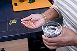 Woman holding dietary supplements in the one hand and a glass of water in the other.
