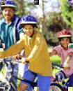 Family riding bicycles while wearing helmets