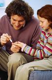 parent checking child's blood glucose level