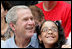 President George W. Bush poses for a photo with a fan in the stands Monday, June 30, 2008, during the opening game of the 2008 Tee Ball season between the Cramer Hill Little League Red Sox of Camden, N.J., and the Jose M. Rodriguez Little League Angels of Manatí, Puerto Rico, on the South Lawn of the White House.