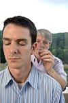 Acupuncturist inserts  needles into a man's ear. © Bob Stockfield
