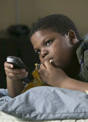 photo of child watching TV and eating
