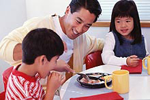 photo of a man and two children eating