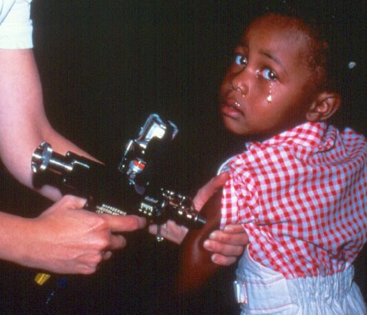 Photo of a teary child being vaccinated using a Ped-O-Jet® needle-free jet injector, circa 1970s.