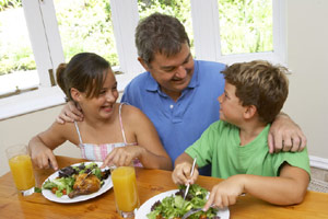 photo of 2 kids and man eating salad and baked chicken