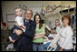 President George W. Bush holds 15-month-old James Jensen, son of Purple Heart recipient U.S. Army Cpl. Isaac Jensen of Layton, Utah, background-right, while posing for a photo Monday, Dec. 22, 2008 with Cpl. Jensen, his wife, Bethany and his mother, Eva Francis, right, during President Bush's visit to Walter Reed Army Medical Center in Washington, D.C. Jensen is recovering from injuries sustained while serving in support of Operation Iraqi Freedom. White House photo by Eric Draper