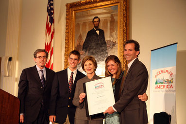 Mrs. Laura Bush presents the Fifth Annual Preserve America History Teacher of the Year award to David Mitchell, right, Friday, Oct. 24, 2008, at the Union League Club in New York City. She is joined by Dr. James Basker, President, Gilder Lehrman Institute of American History, left, and David Mitchell's students from Masconomet Regional High School in Boxford, Mass., David Burbank, 17, and Molly Byman, 18. The award notes the importance of teaching history and highlights the Preserve America initiative. White House photo by Chris Greenberg