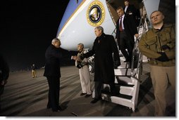 """President George W. Bush is greeted as he deplanes Air Force One Monday, Dec. 15, 2008, after arriving in the pre-dawn hours in Afghanistan. The President visited with troops at Bagram Air Base, thanking them for their service and telling them, """"I am proud to be with brave souls serving the United States of America.""""  White House photo by Eric Draper"""