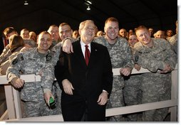 """President George W. Bush pauses for photos with troops at Bagram Air Base Monday, Dec. 15, 2008, in Afghanistan. The President made the pre-dawn visit to the base before meeting with President Hamid Karzai in Kabul. During his remarks to the troops, the President said, """"What you're doing in Afghanistan is important, it is courageous, and it is selfless. It's akin to what American troops did in places like Normandy and Iwo Jima and Korea. Your generation is every bit as great as any that has come before. And the work you do every day is shaping history for generations to come.""""  White House photo by Eric Draper"""