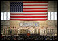 With an American flag as a backdrop, President George W. Bush addresses military personnel Monday, Aug. 4, 2008, during a stop in Alaska at Eielson Air Force Base, en route to South Korea.  White House photo by Chris Greenberg