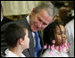 President George W. Bush talks with sixth grade student Mariano Ramos, 11, left, and seventh grader Amber McCarthy, 12, Monday, Jan. 7, 2008, during a visit to the Horace Greeley Elementary School in Chicago. White House photo by Joyce N. Boghosian
