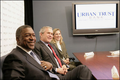 President George W. Bush sits with Bob Johnson, founder and chairman of the RLJ Companies, and Kathy Boden, right, president and CEO of Blue House Water Solutions , during a meeting to discuss the economy with small business owners and community bankers, Monday, Oct. 23, 2006 at the Urban Trust Bank in Washington, D.C. White House photo by Eric Draper