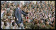 """President George W. Bush acknowledges his audience as he enters the staging area Tuesday, Nov. 25, 2008, at Fort Campbell, Ky., home of the 101st Airborne. The President told the troops, """"We are blessed to have defenders of such character and courage. I'm grateful to the families who serve by your side. And I will always be thankful for the honor of having served as the Commander-in-Chief."""" White House photo by Eric Draper"""