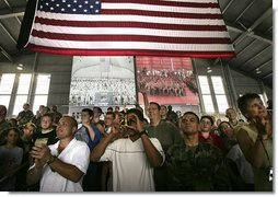 MacDill Air Force Base mIlitary personnel listen to President George W. Bush deliver remarks as two screens display a live feed of military personnel in Afghanistan, left, and Iraq, Wednesday, June 16, 2004.   White House photo by Eric Draper