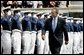 President George W. Bush walks to the stage while saluted by Air Force Cadets during his introduction at the United States Air Force Academy Graduation Ceremony in Colorado Springs, Colorado, June 2, 2004. White House photo by Eric Draper.