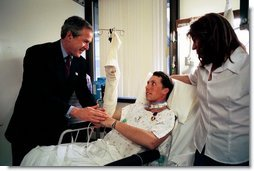 President George W. Bush shakes hands with Army SFC Thomas Douglas of Fayetteville, N.C., after presenting him with the Purple Heart at Walter Reed Army Medical Center in Washington, D.C., Friday, April 11, 2003. Also pictured is Mr. Douglas' wife, Donna Douglas.  White House photo by Eric Draper