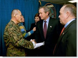 President George W. Bush and Laura Bush attend the U.S. Citizenship Ceremony for Marine Corps Mastery Gunnery Sgt. Guadalupe Denogean of Tucson, Ariz., at the National Naval Medical Center in Bethesda, Md., Friday, April 11, 2003. Pictured at far right, Eduardo Aguirre, Jr., Acting Director of the Bureau of Citizenship and Immigration Services, conducted the ceremony.  White House photo by Eric Draper
