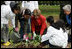 Mrs. Laura Bush helps children plant flowers at the First Bloom Event, Monday, April 21, 2008, during her visit to celebrate National Park week at the Castle Clinton National Monument in New York City.
