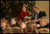 President George W. Bush and Mrs. Laura Bush share a moment with Malik Lawson during the Children's Holiday Performance Monday, Dec. 3, 2007, at the White House. The 7-year-old is the son of TSgt. Sherry Martin, currently serving in Iraq.