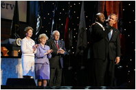 President George W. Bush puts his arm around Singer Bebe Winans as he sings 'God Bless America' during the 'Saluting Those Who Serve' event at the MCI Center in Washington, D.C., Tuesday, Jan. 18, 2005. Also pictured are, from left, Laura Bush, Lynne Cheney, and Vice President Dick Cheney.