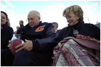 Vice President Dick Cheney signs a football for a Natrona County High School student while watching the school's homecoming game with his high school sweetheart, Lynne Cheney, in Casper, Wyo., Sept. 20, 2002.