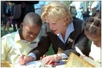 A second grade boy looks on as Mrs. Cheney demonstrates how the founding fathers used quill pens to sign the U.S. Constitution during Constitution Day at the Naval Observatory Sept. 17, 2002. In additions to signing the Constitution, children also learned about 18th century coins and making coin rubbings, created tricorn hats like those worn in the 1700s and played Constitution-era games.